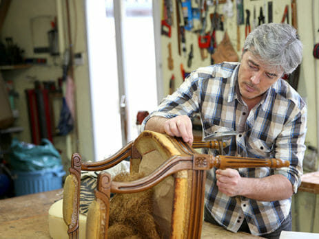 A man upholstering a chair
